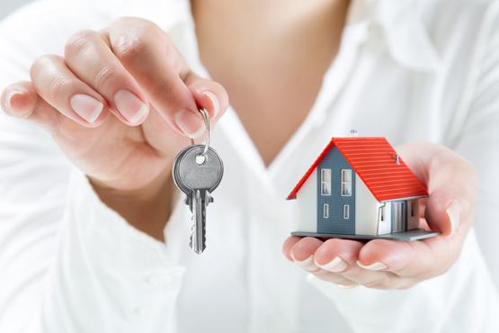 Donna con chiavi in una mano e piccola casetta nell'altra